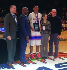 Armando Dunn (center) is awarded the PSAL's Student-Athlete Award for having the highest GPA on his team.